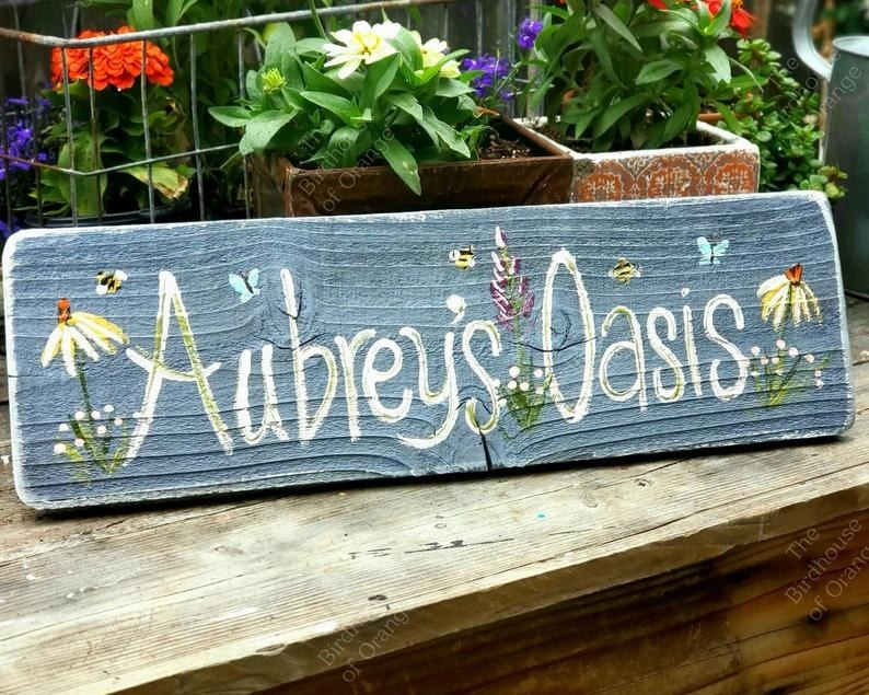 """rectangle blue sign that says """"Aubrey's Oasis"""" with painted flowers"""