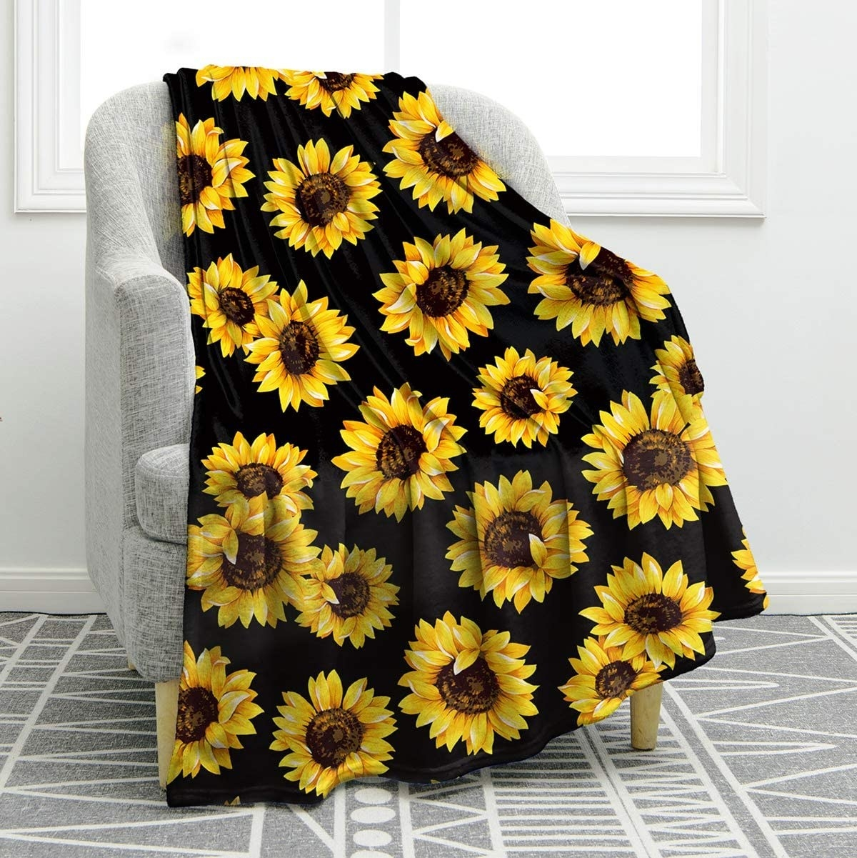 The blanket with a sunflower pattern draped over a chair