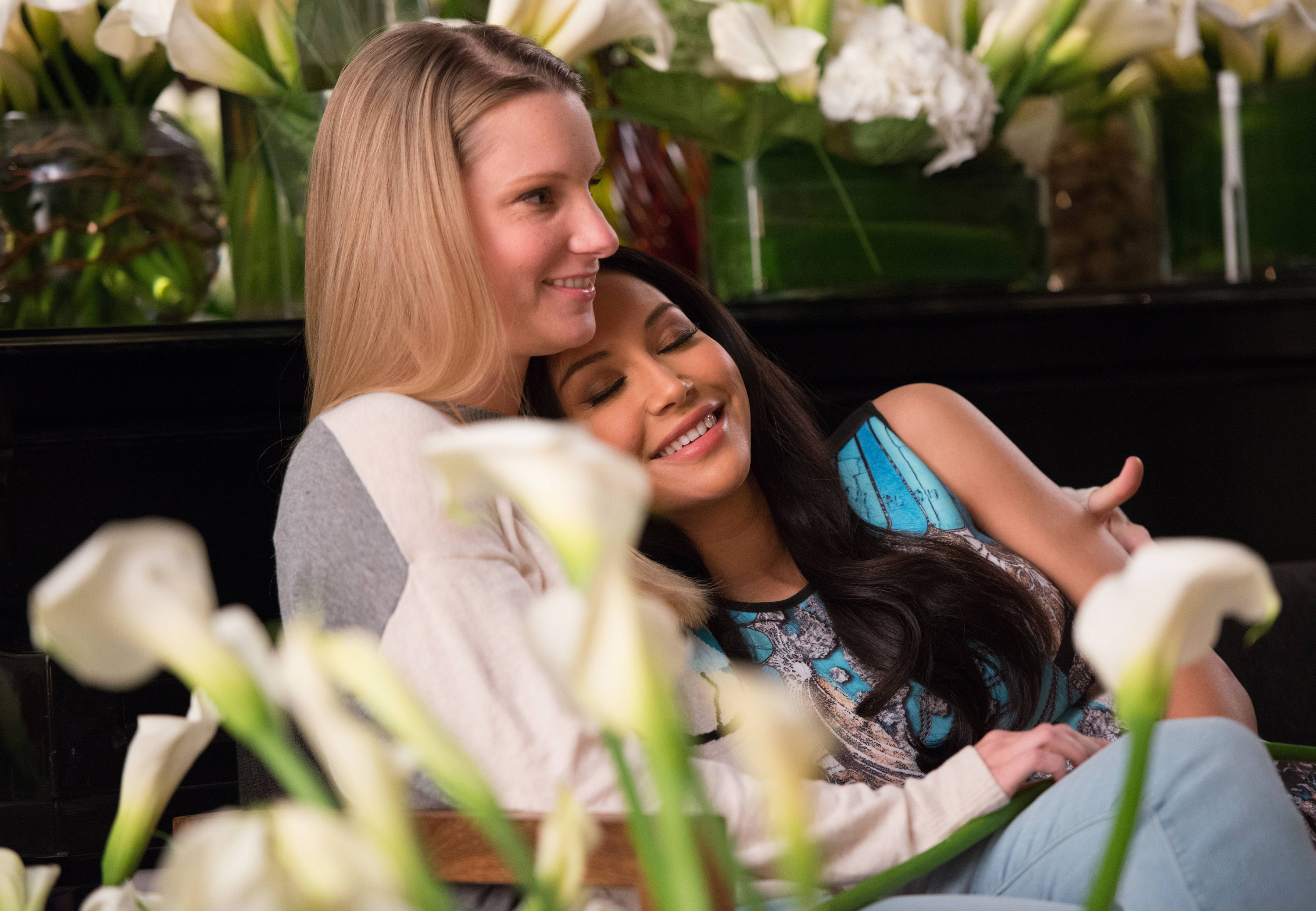 Heather and Naya cuddling in a scene from Glee