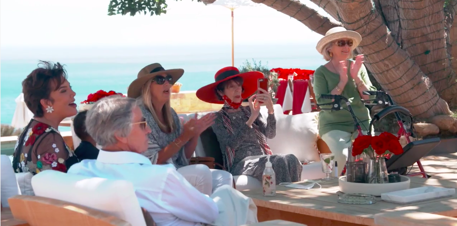 Adults sit together at a seaside patio, none of them wearing masks