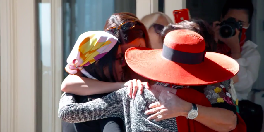 Four adults join together in a group hug