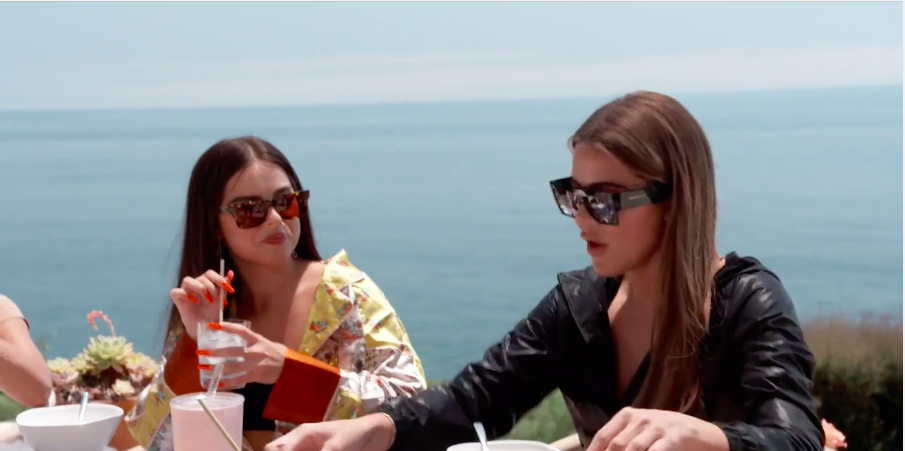 Khloé and Addison wear sunglasses at a dining table by the ocean