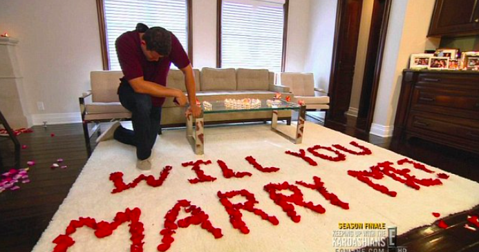 """Kris kneels on a rug in front of rose petals spelling out the words """"will you marry me?"""""""