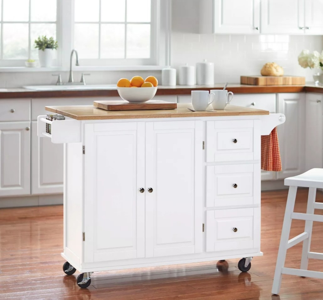 A white kitchen island cart with wooden top and storage cabinets and drawers