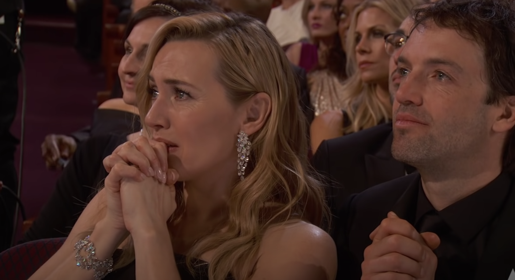 Kate clasping her hands to her face