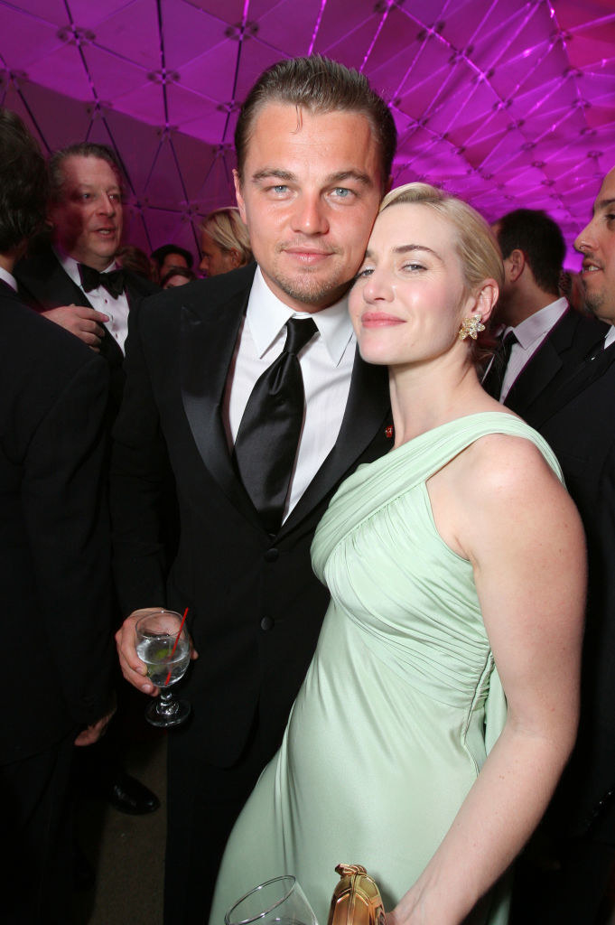 Leo and Kate looking into the camera and touching cheeks