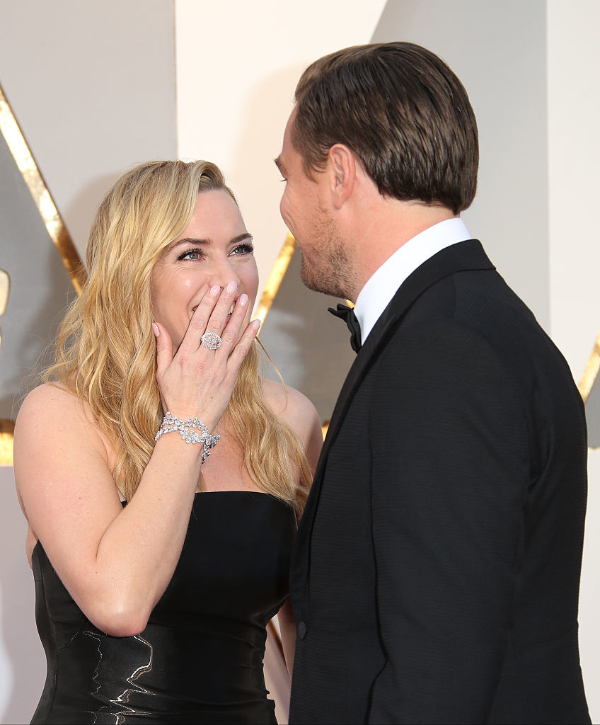 Kate smiling at Leo with her hand over her mouth