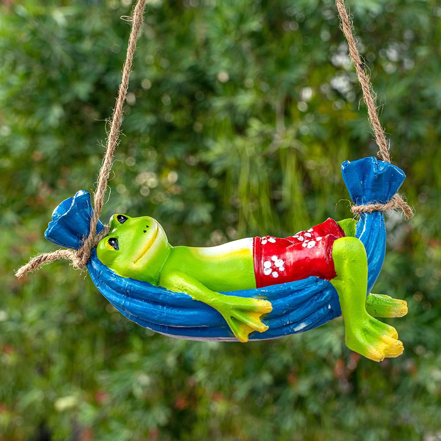 A  figurine of a frog on a hammock