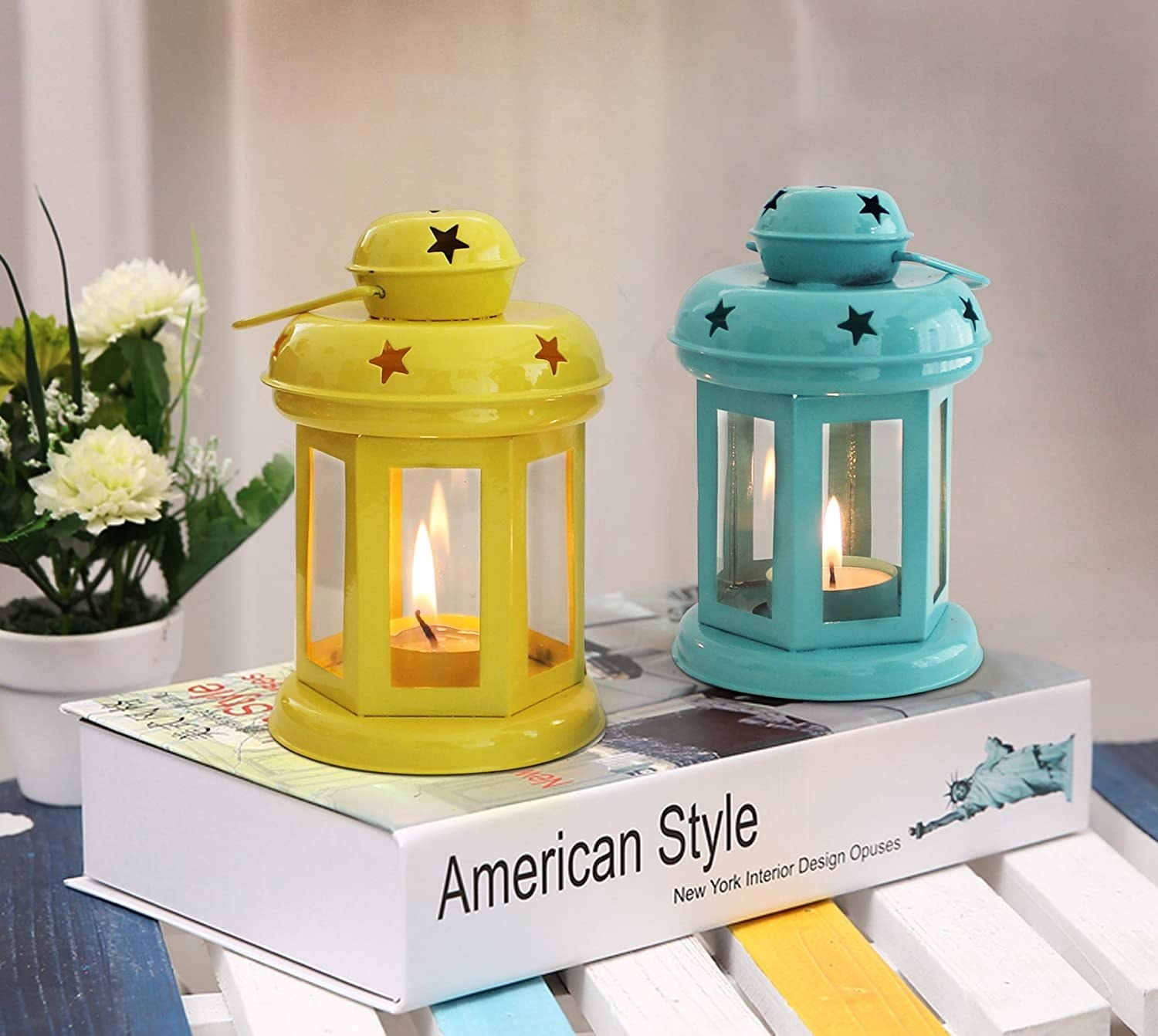 Yellow and turquoise lanterns kept on a book