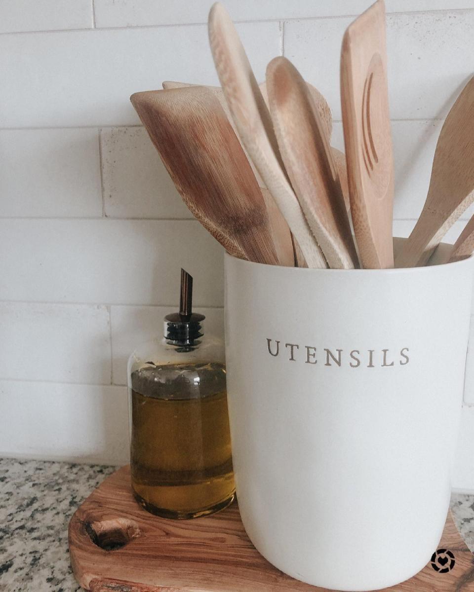 "a white stone utensil holder with ""utensils"" written on it in uppercase letters"