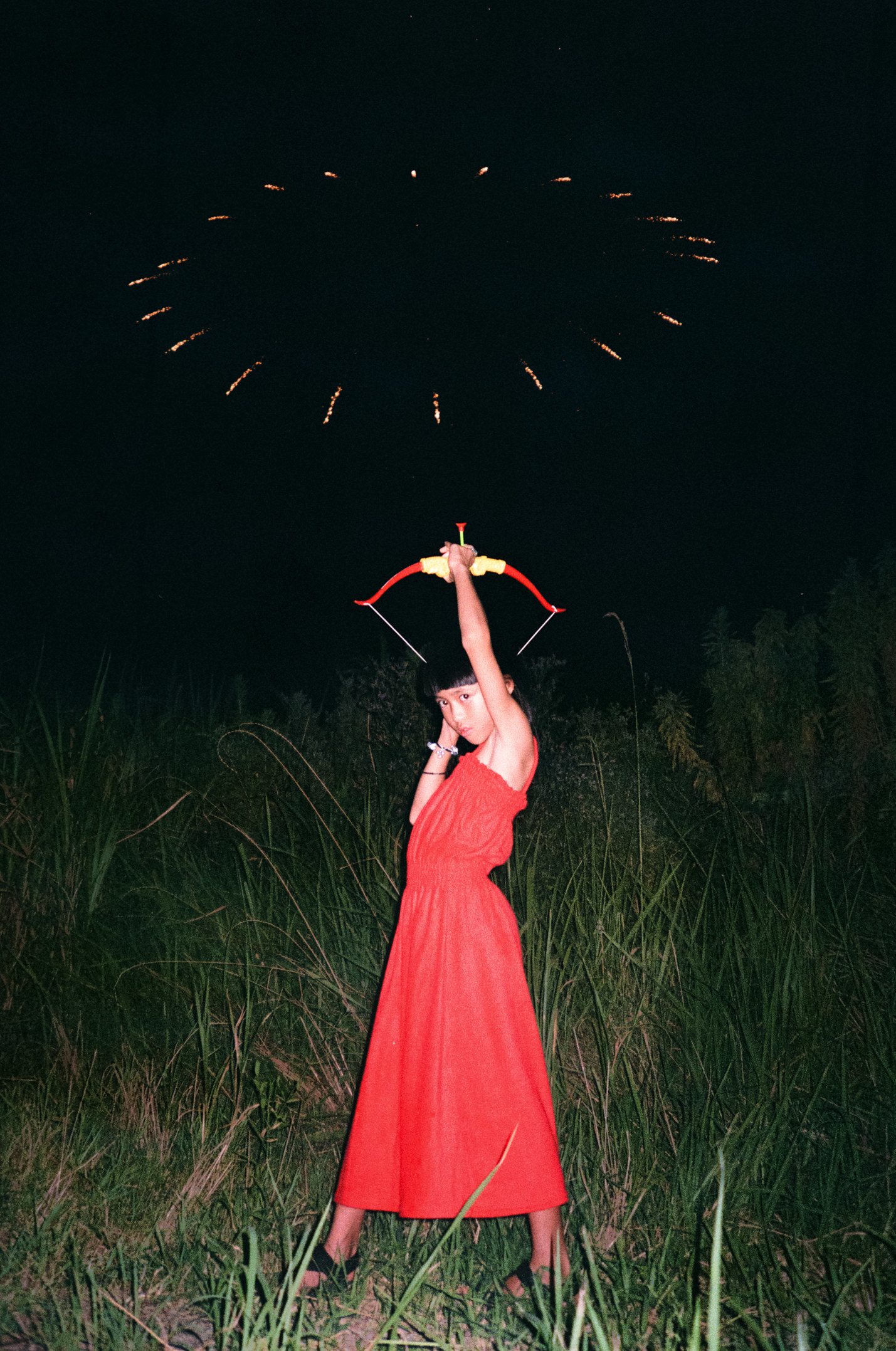 The photographer's daughter shooting an arrow upwards into fireworks