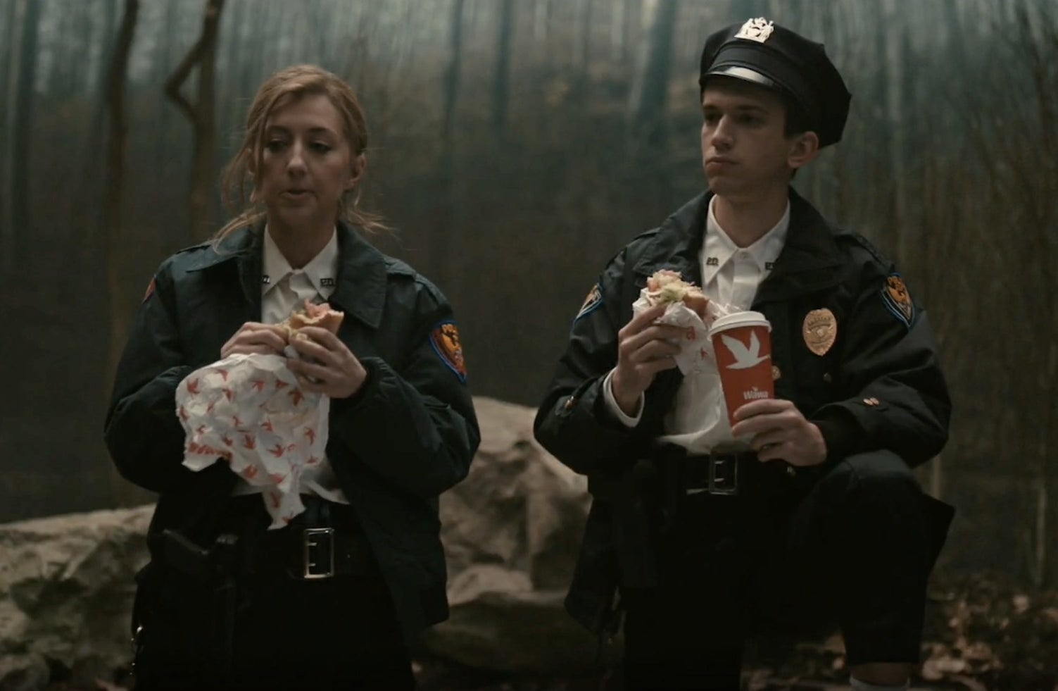 SNL cast members in cop uniform with Wawa sandwiches and coffee