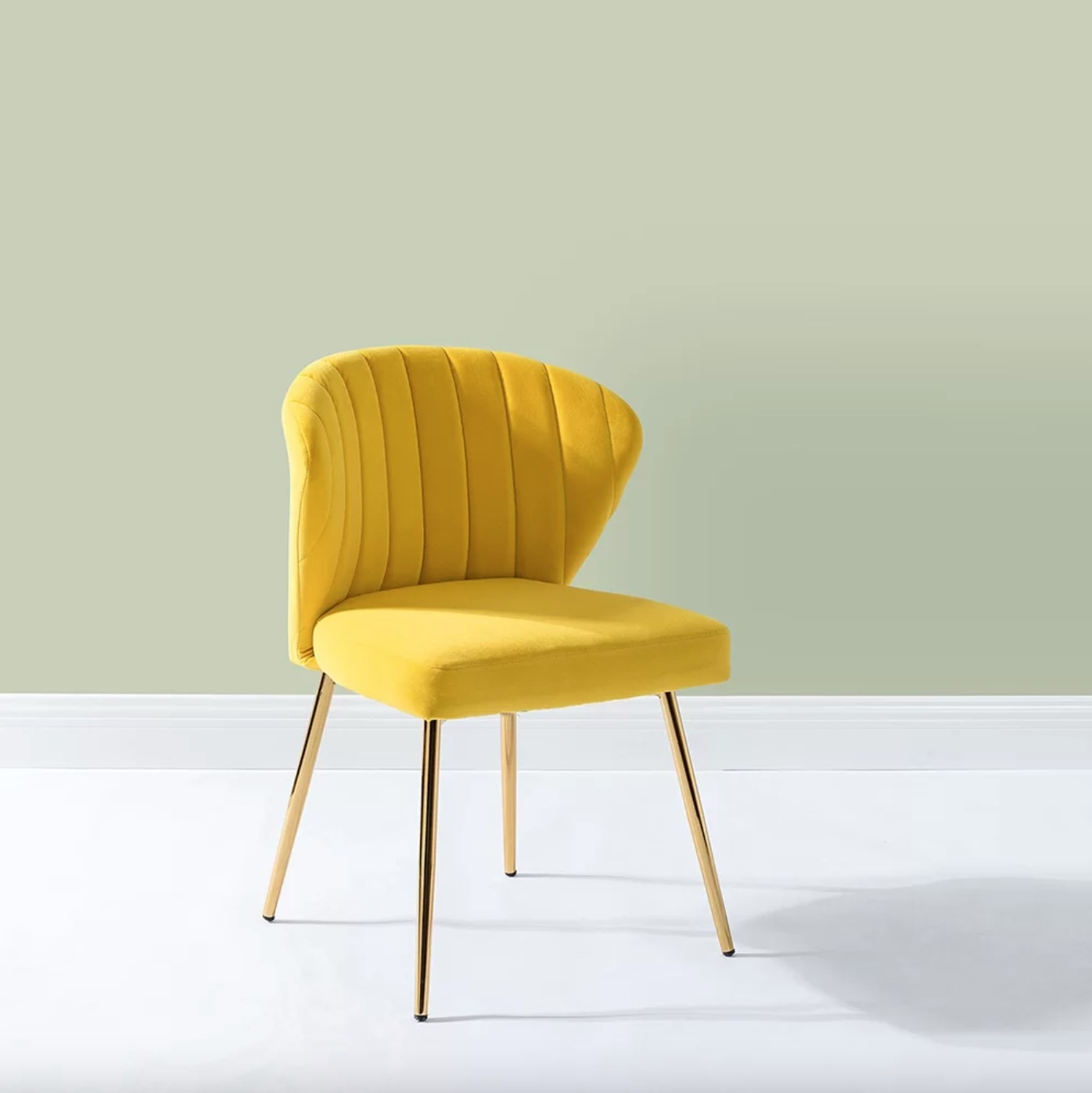 The tufted velvet side chair in yellow with gold legs