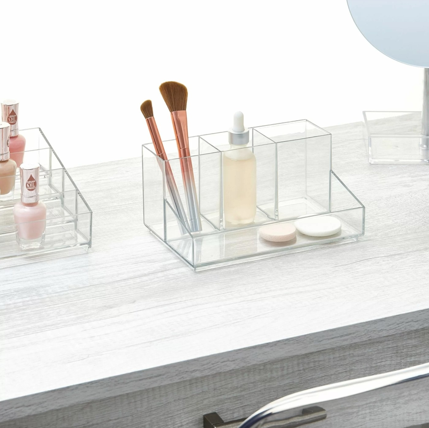 The cosmetic makeup organizer in clear plastic holding brushes