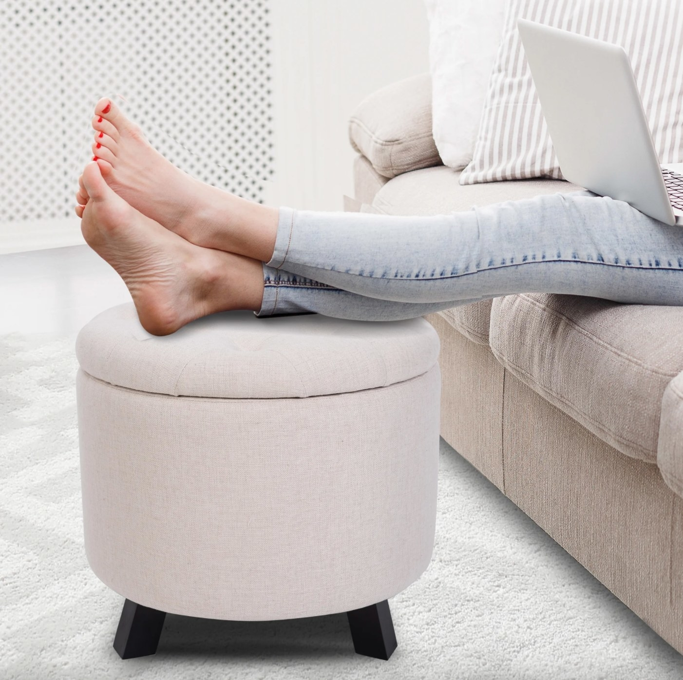 The tufted storage ottoman in beige with legs resting on them