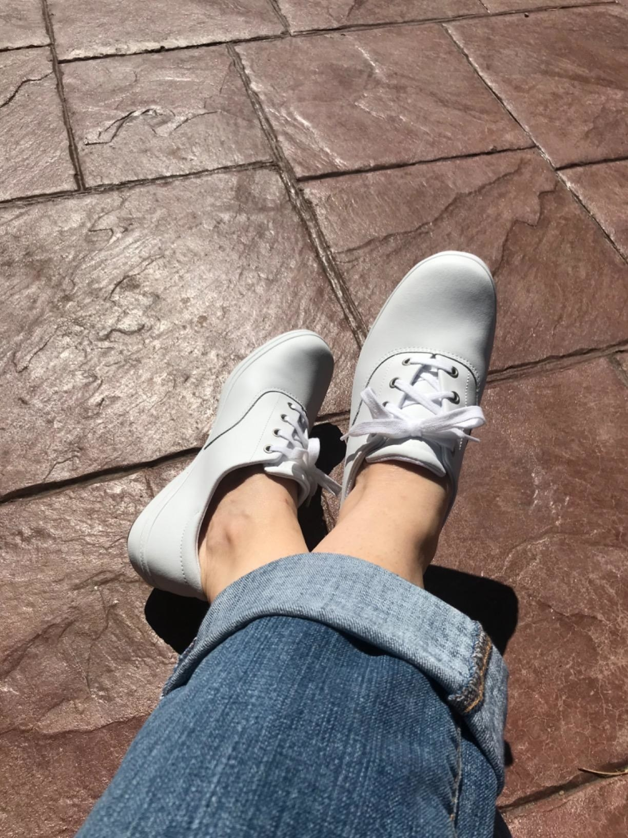 Reviewer wearing white Grasshoppers sneakers