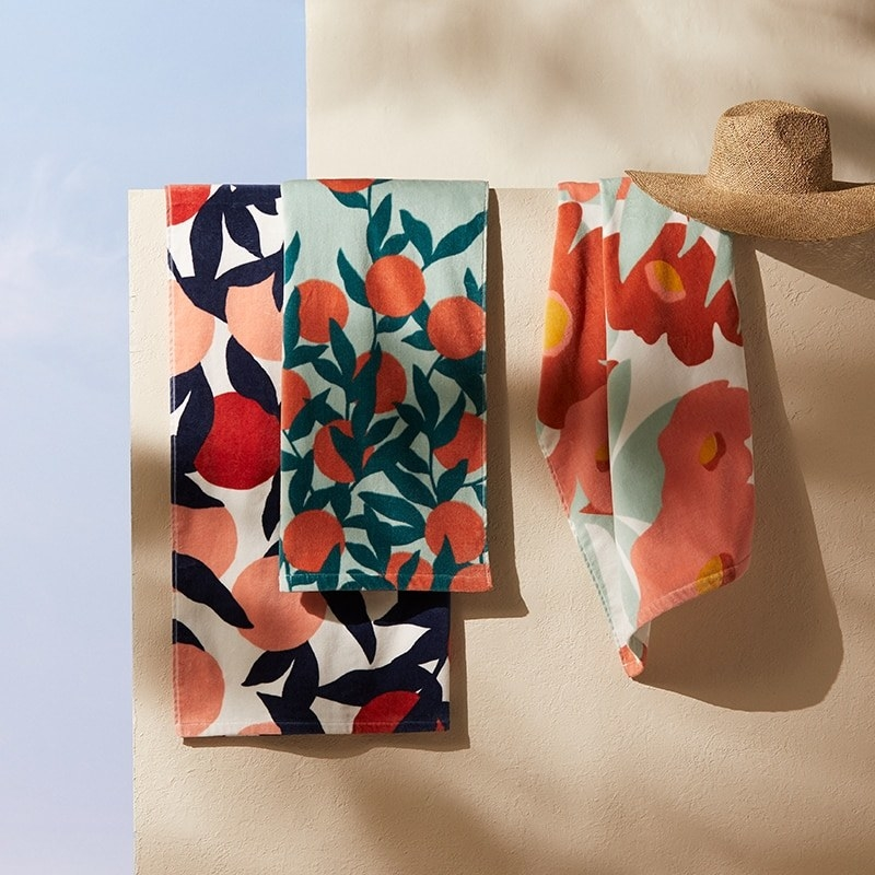 Three hanging towels with vibrant floral patterns on each