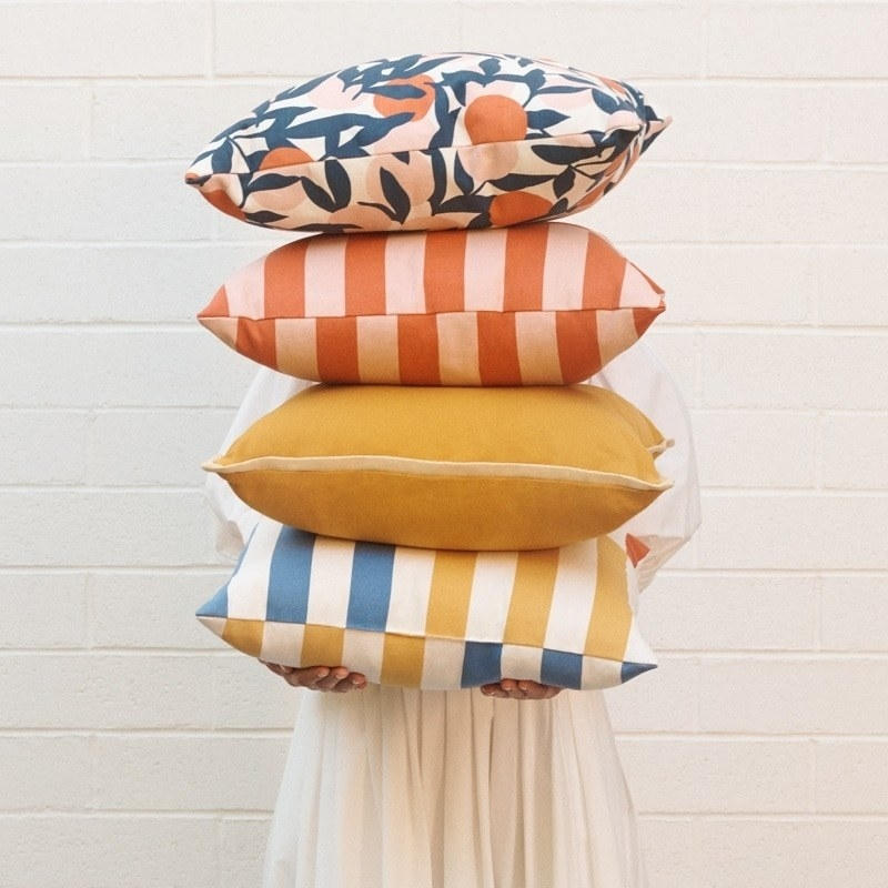 A person holding four vibrant pillows