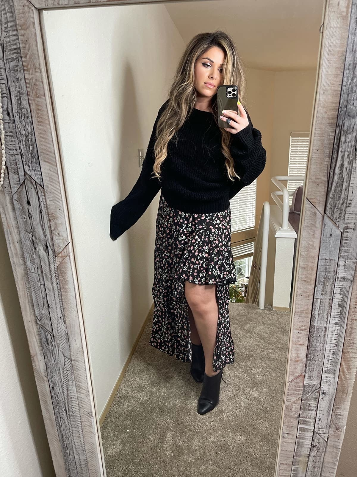 image of reviewer wearing the z-black pattern BTFBM boho floral high low skirt with a black sweatshirt