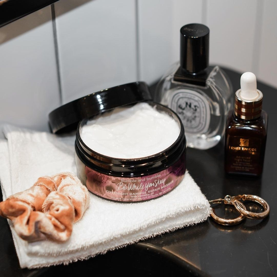 A jar of the hair mask on a vanity next to other skincare and jewellery