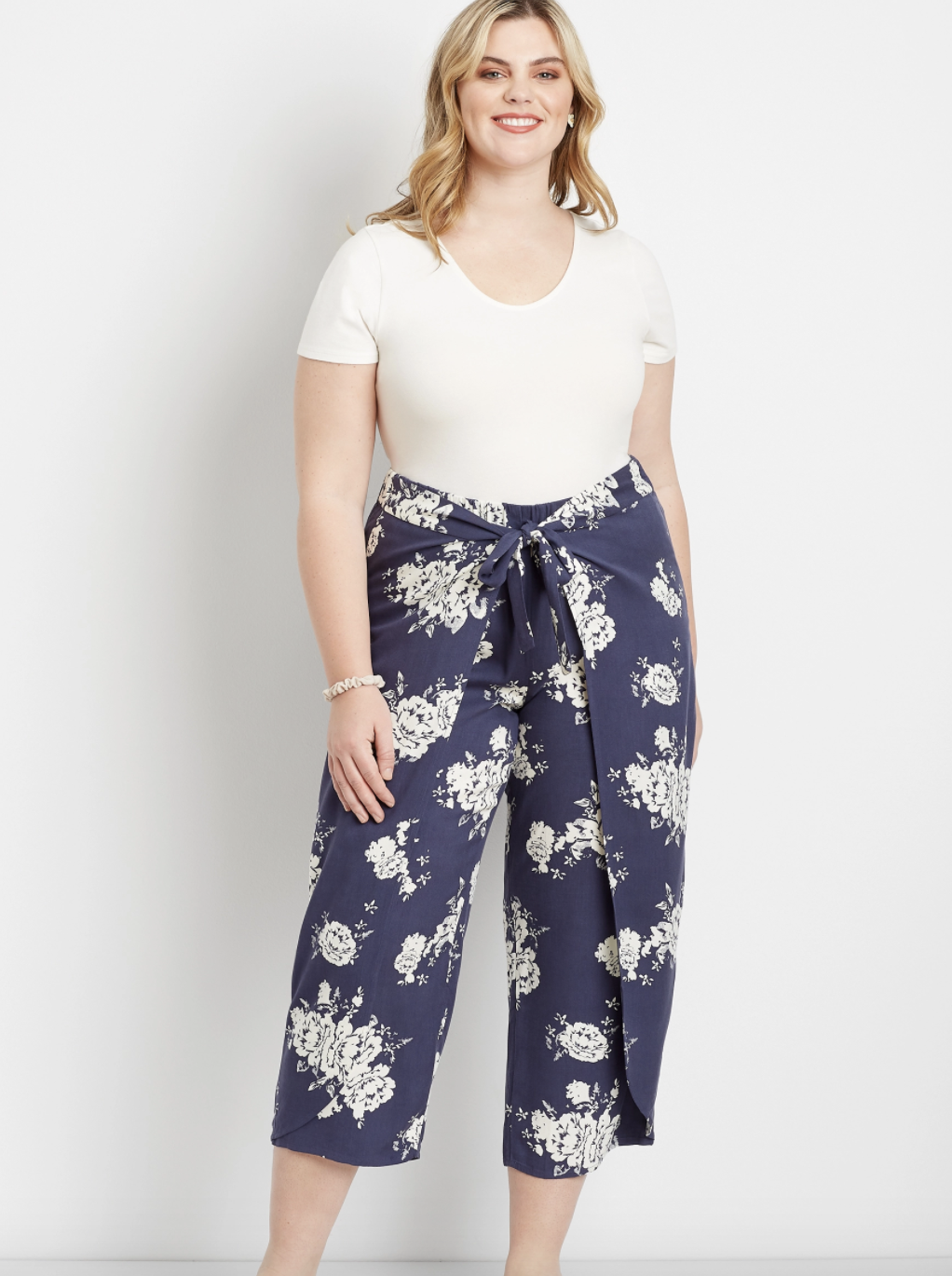 plus size model wearing the navy floral flyaway pants with a white tee