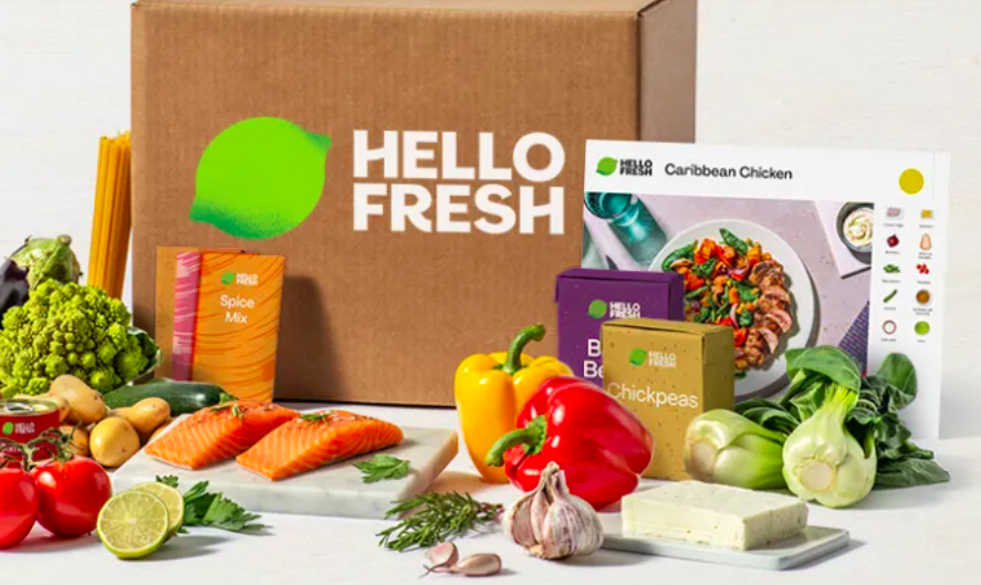 A Hello Fresh box surrounded with ingredients and recipes