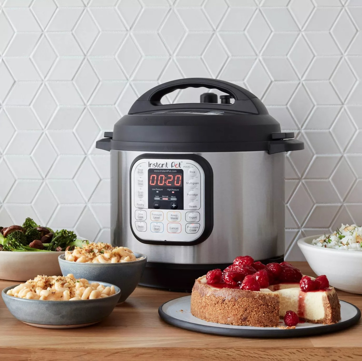 the instant pot surrounded by mac and cheese, cheesecake, and salad