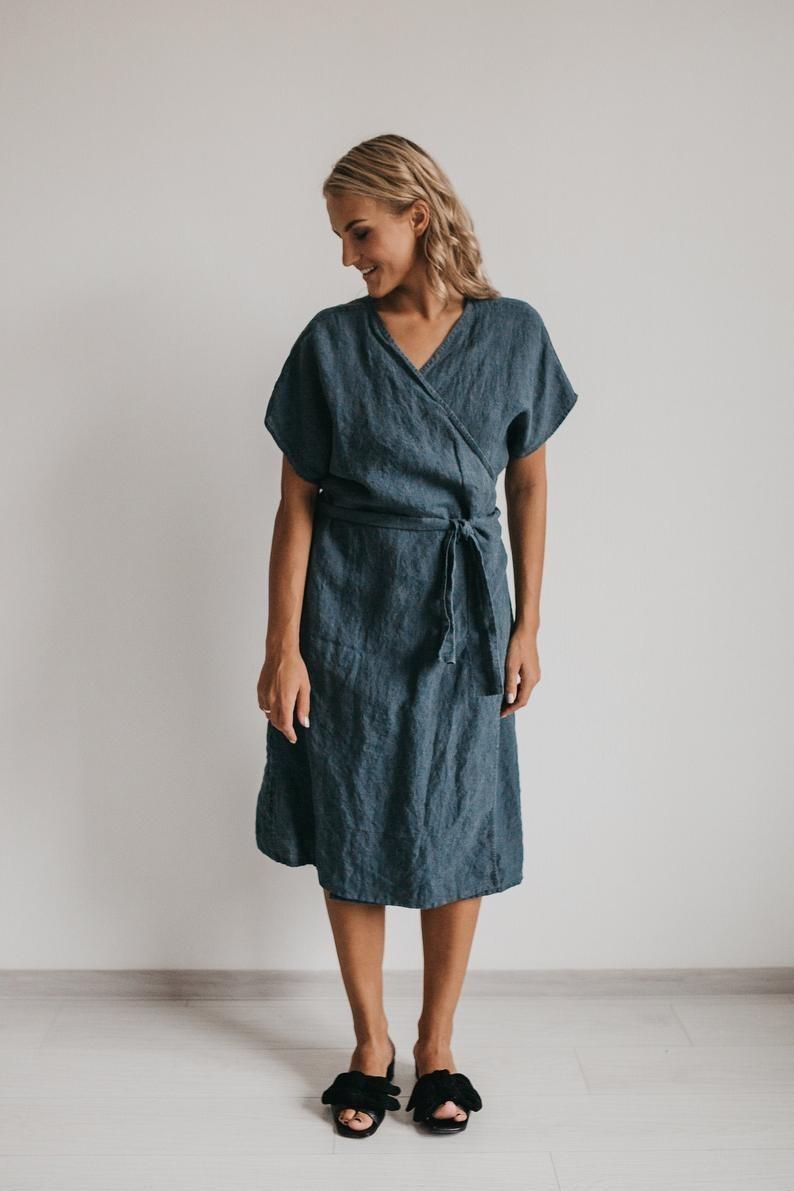 model wearing oversized, below-the-knee, dark blue wrap dress