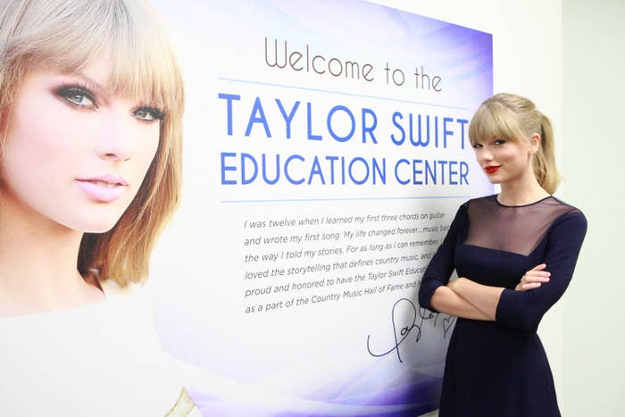 Taylor stands in front of a sign that says welcome to the Taylor Swift education center