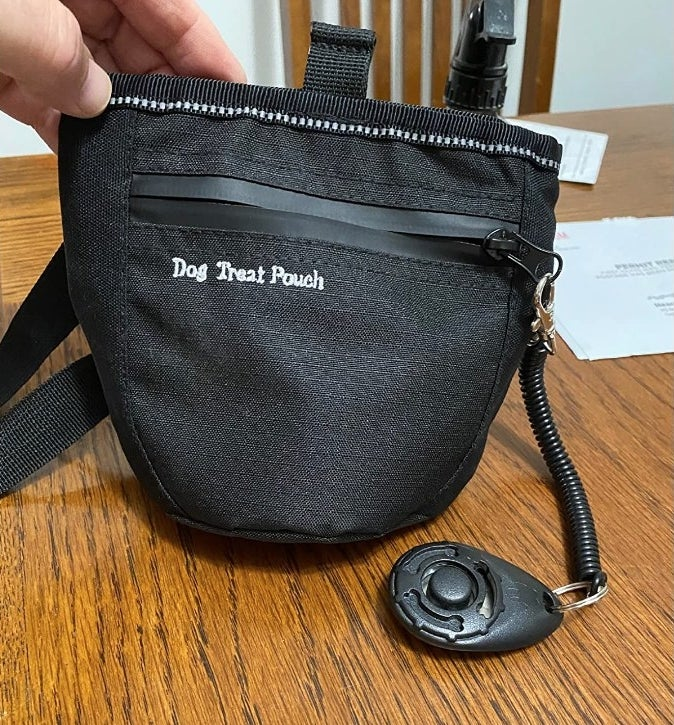 A reviewer displaying their dog treats training pouch with an attached training clicker