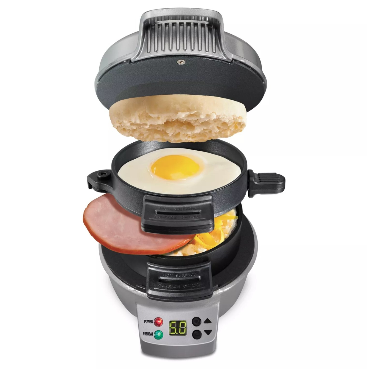 the sandwich maker with an english muffin, egg, ham slice, and cheese in the appliance