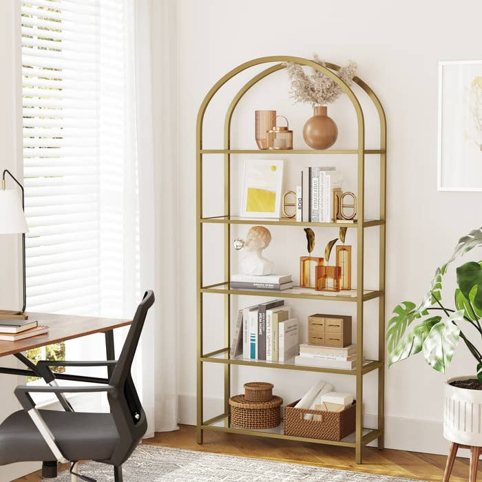 gold arched bookcase displaying various amber, tan, and cream colored decor