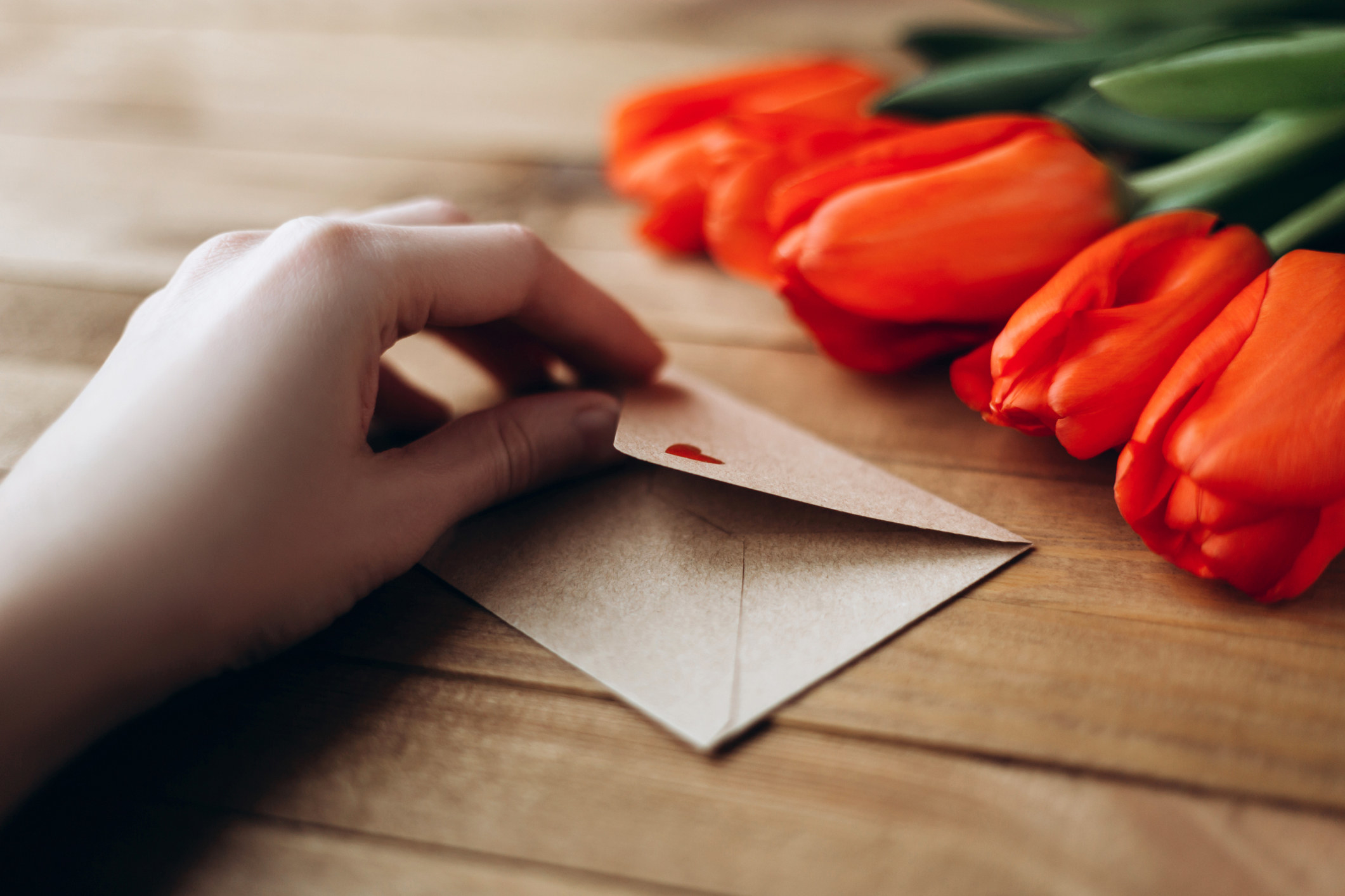 Someone opens a romantic card that has a heart on the envelope
