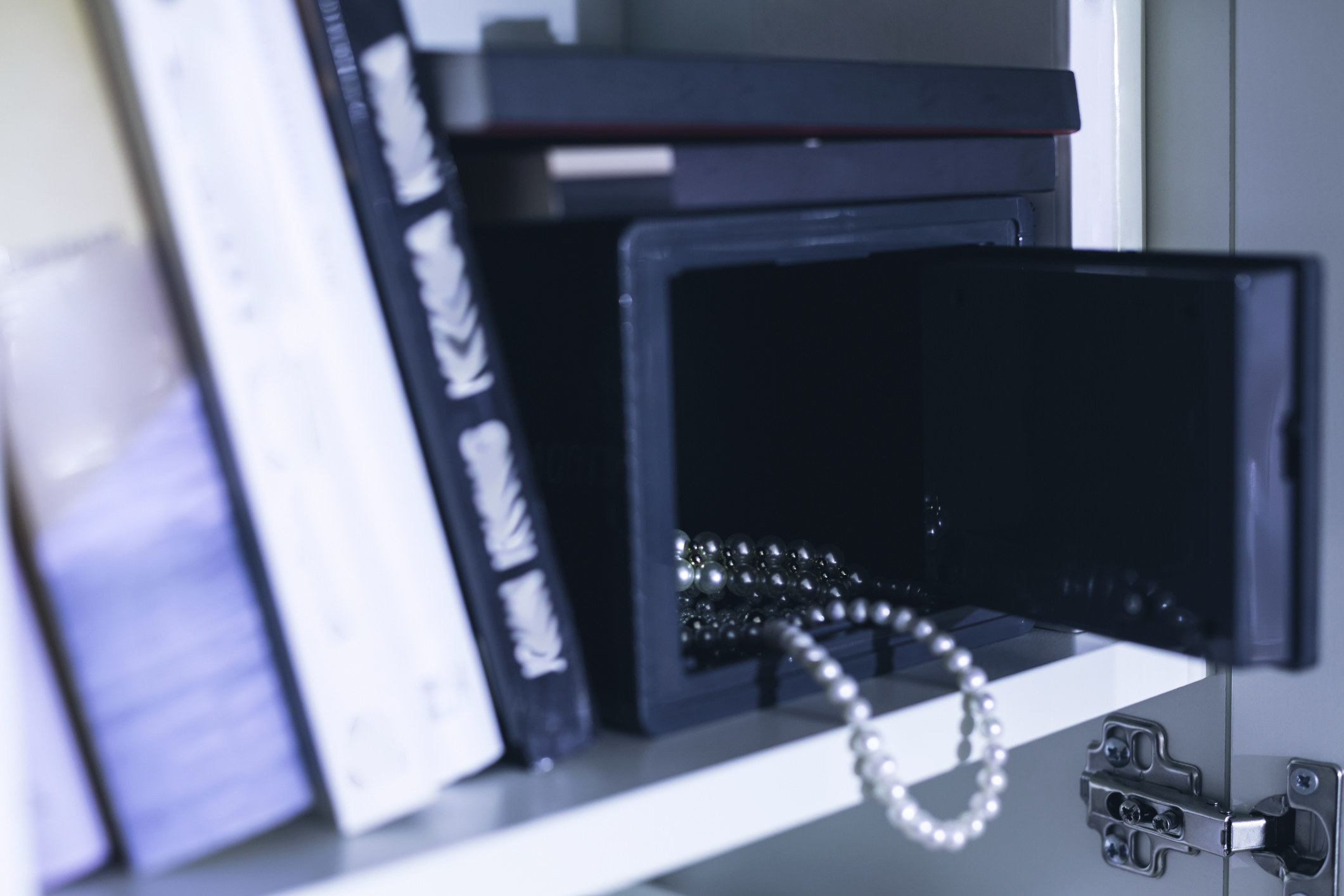 Image of open domestic safe on shelf with expensive jewelry falling out