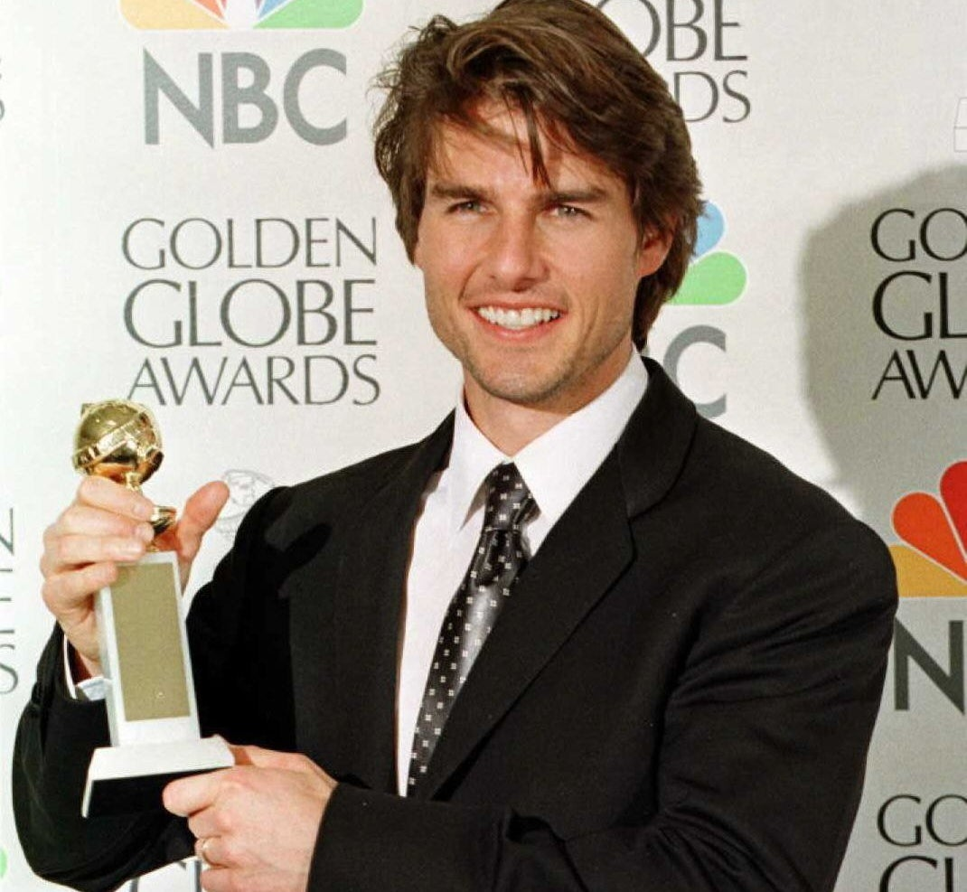 Tom holds up his Golden Globe Award at the time he won it