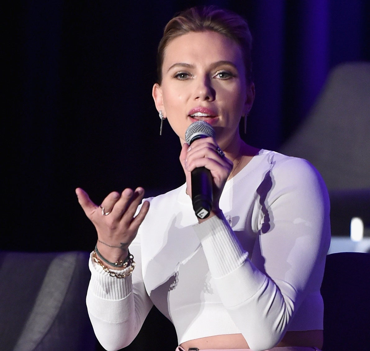 Scarlett speaks onstage at a press conference