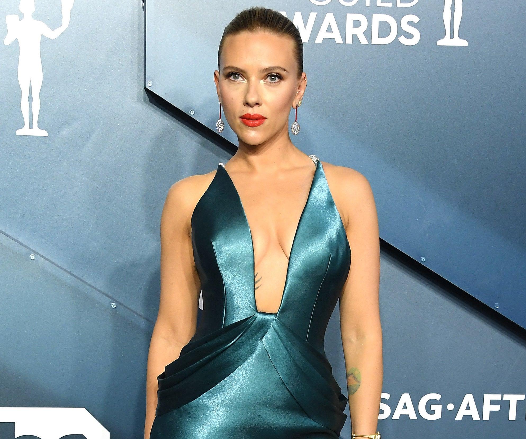 Scarlett wears a teal silk dress