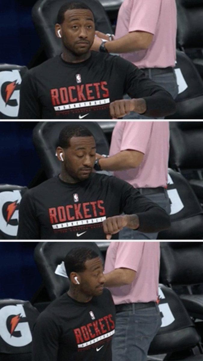 A basketball player looking at his watch and shaking his head