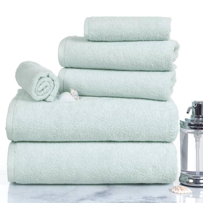 Teal bath towels sitting on bathroom sink