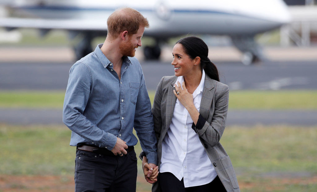 Prince Harry (L) and Meghan Markle arrive at Dubbo Airport
