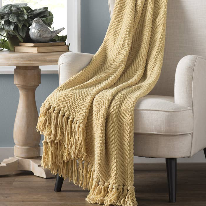 Yellow blanket draped over accent chair