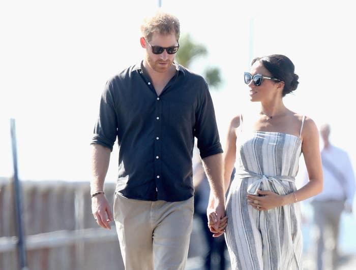 Prince Harry (L) and Meghan Markle walk along the picturesque Kingfisher Bay Jetty