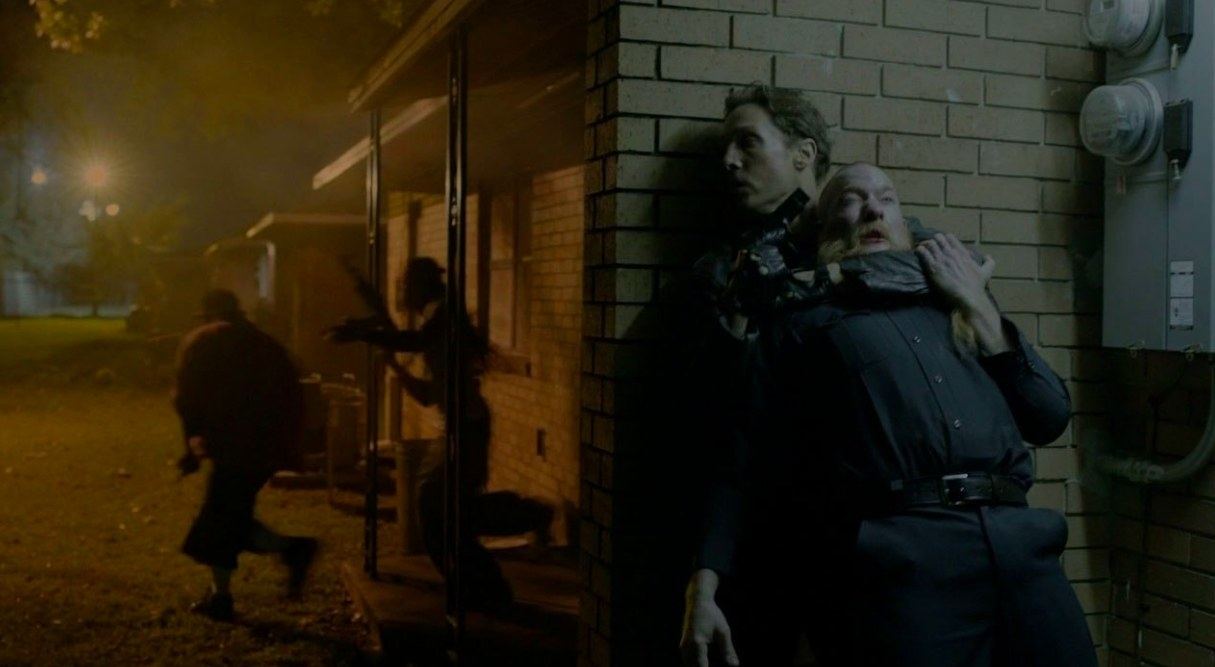 Rust stands against the wall with his gun pointed to a man's head as two men run from the building behind him
