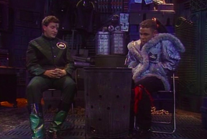 Rimmer and Lister sit in front of a fire in a barrel in a spaceship