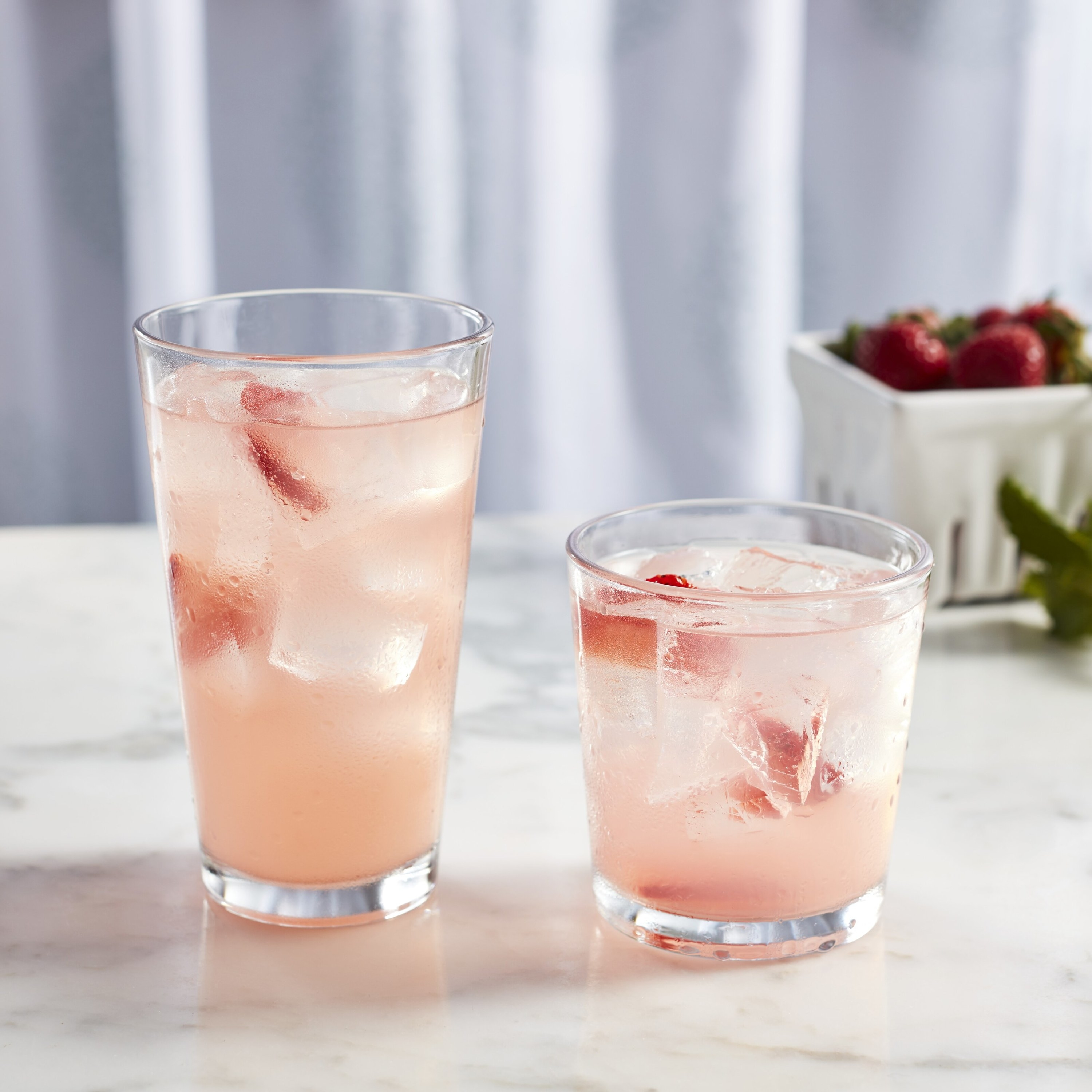 Tall and short glasses with strawberry lemonade inside