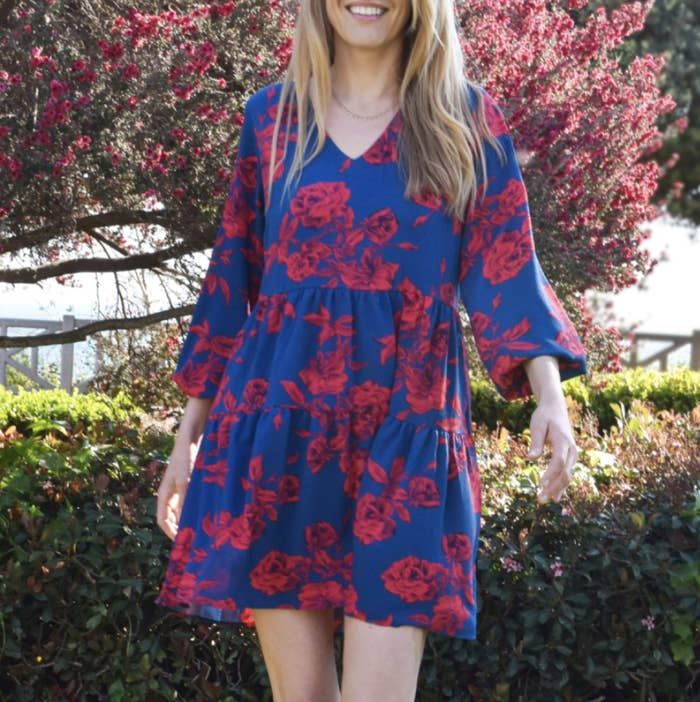 reviewer wearing the long sleeve version of dress with a rose print on it