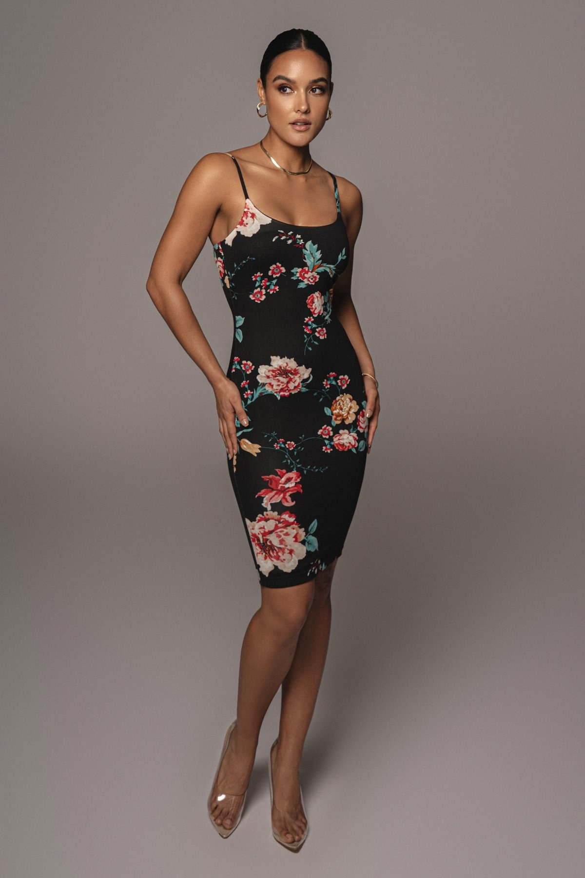 model wearing spaghetti strap black mini dress with a large floral pattern on it