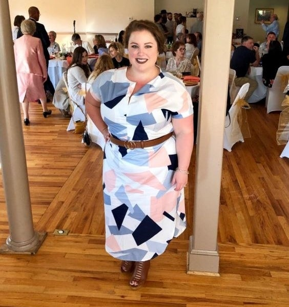 Reviewer wearing the geometrically patterned dress in blue, pink, and white