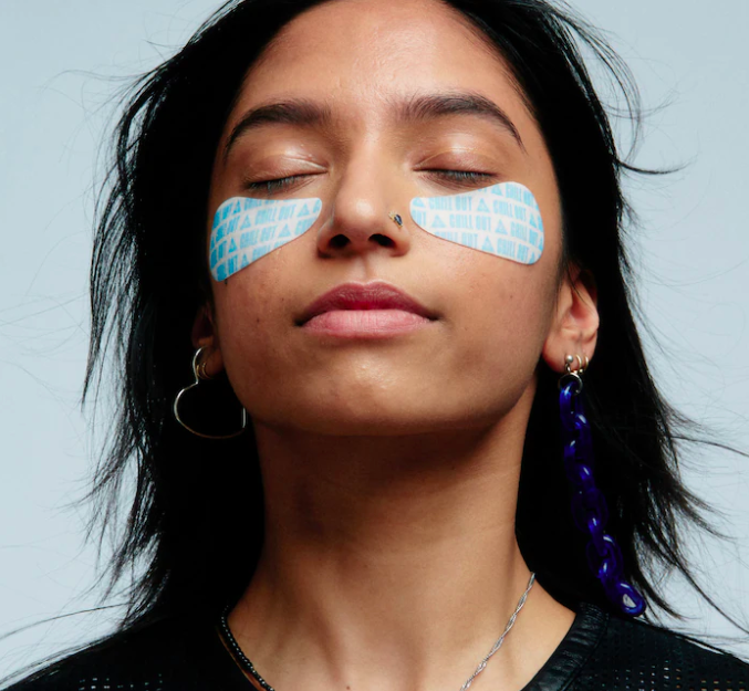 A person wearing the eye masks; their eyes are closed and they look blissful