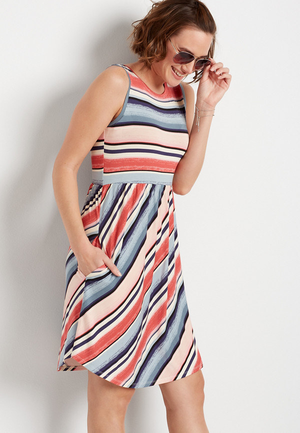 model wearing the sleeveless above the knee diagonal blue, white, and orange stripe dress with a hand in one of the pockets
